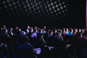 conference attendees sitting in a dark auditorium room.